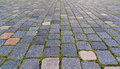 Cobbled pavement backgorund with green grass Royalty Free Stock Photo
