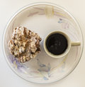 Cobblestone pastry and cup of coffee on patterened plate white bkg Royalty Free Stock Photography