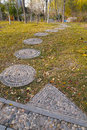 Cobblestone walkway the in autumnal grassplot Stock Photos