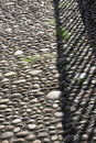 Cobblestone walkway surface with shadows from nearby railing Royalty Free Stock Photo