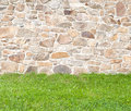 Cobblestone wall old brown and gray with grass in the foreground Royalty Free Stock Image