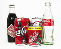 Coca cola bottles and cans variety of red yellow white in varying sizes first produced in the th century is a Stock Photo