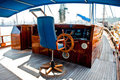 Cockpit inside a boat with a wood wheel.