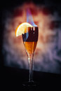 Cocktail with alcohol and flame in wineglass vintage stylized photo Stock Image