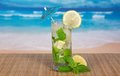 Cocktail on a bamboo cloth green of alcohol with an umbrella lemon and spearmint against the sea Royalty Free Stock Photos