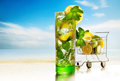 Cocktail fresh tropical and basket with lemons and mint on sea background Stock Photo