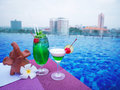 Cocktail glasses at swimmimg pool with city view