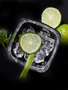 Cocktail with ice and lime on black background Stock Images