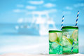 Cocktail with ice, rum, lemon and mint   in a  glass  on beach Royalty Free Stock Photo