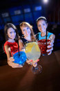 Cocktail party group of happy beautiful young female friends celebrating in a nightclub with glasses of focus on hands Stock Photo