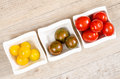 Cocktail tomatoes in yellow green and red bowls on a wooden board Royalty Free Stock Photos