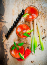 Cocktails made of tomatoes, vodka, ice, lime, pepper , salt and snack with celery and black olives on rustic background . Royalty Free Stock Photo