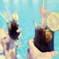 Cocktails in pool bar hands holding with water background summer resort vacation refreshment relaxation concept Royalty Free Stock Photography