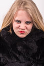 Cocky angry young cute young woman in fur jacket that looks into the camera with a white background behind Stock Photos