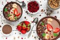 Cocoa or chocolate and banana protein smoothie bowls with granola, strawberry and pomegranate seeds served for breakfast Royalty Free Stock Photo