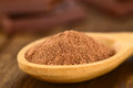Cocoa powder on wooden spoon with chocolate pieces in the back very shallow depth of field focus one third into the Stock Photography