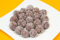Coconut balls unbaked chocolate coated in on white plate Stock Photography