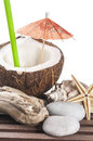 Coconut cocktail with green drinking straw and umbrella pebbles seastar seashell Stock Images