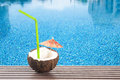 Coconut cocktail with green drinking straw and umbrella by the swimming pool Stock Image