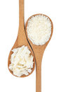 Coconut dessicated and flaked in wooden spoons over white background Stock Photos
