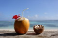 Coconut Drink and Coconut Pieces On wooden Table With Beach On Background, Exotic Island Vacation Royalty Free Stock Photo