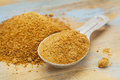 Coconut palm sugar unrefiined measuring tablespoon and pile on wood surface Stock Photos