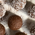 Coconut rum balls being covered with grated on plate photographed overhead with natural light selective focus focus on the Royalty Free Stock Image