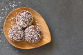 Coconut rum balls on small wooden plate photographed overhead om slate with natural light selective focus focus on the top of the Royalty Free Stock Images