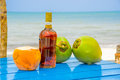 Coconuts and liquor bottle on table by the beach Royalty Free Stock Photo
