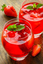 Coctail refreshing summer drink with strawberry in jug and glasses on the vintage wooden table Stock Photography