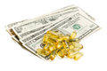 Cod liver oil gel capsules with dollars Royalty Free Stock Photos