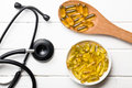 Cod liver oil gel capsules and stethoscope Stock Photography