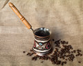 Cofee kettle and beans isolated on textile material Royalty Free Stock Images