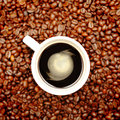 Coffe cup and beans of fresh coffee from above surrounded by Royalty Free Stock Image