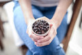 Coffee bean in cup on woman hand Royalty Free Stock Photo
