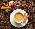 Coffee beans background with cofee cup, cinnamon, and chocolate Royalty Free Stock Photo