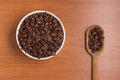 Coffee beans into a bowl and spoon. Coffea arabica Royalty Free Stock Photo