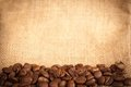 Coffee beans on burlap material Stock Photos