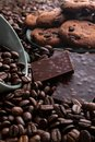 stock image of  Coffee beans with chocolate and cookies in a cup and a plate