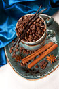 Coffee beans with cinnamon and vanilla in a blue cup on a vintage board Stock Photo