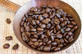 Coffee beans in a copper pan an old on the background of natural fiber mat Royalty Free Stock Image