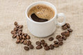 Coffee beans and cup of coffee on burlap Royalty Free Stock Photo