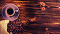 Coffee beans and a cup of coffee on a wooden background.