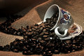 Coffee beans cup full of and spilling out of on the burlap Royalty Free Stock Images