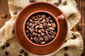 Coffee beans in a cup on a wooden table Stock Images