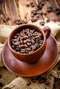 Coffee beans in a cup on a wooden table Stock Photos