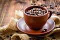 Coffee beans in a cup on a wooden table Royalty Free Stock Image