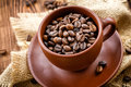 Coffee beans in a cup on a wooden table Royalty Free Stock Photos