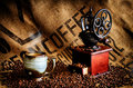 Coffee beans and grinder cup of steaming hot with bag in background Royalty Free Stock Photos