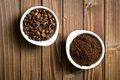 Coffee beans and ground coffee in bowls top view of on wooden table Royalty Free Stock Photography